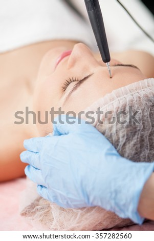 Close up of arms of skillful beautician touching equipment to female forehead. The woman is lying with relaxation. Here eyes are closed with pleasure - stock photo
