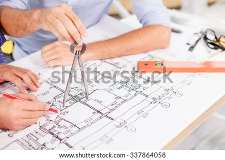 Close up of arms of two engineers projecting a new construction. They are sitting at the table and working with sketch of building - stock photo