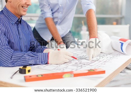 Close up of arms of two successful engineers designing the building. The senior worker is sitting at the table and drawing sketch. The man is smiling - stock photo