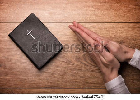 Close up of arms of young woman praying near the Bible. Her hands are clasped on the table - stock photo