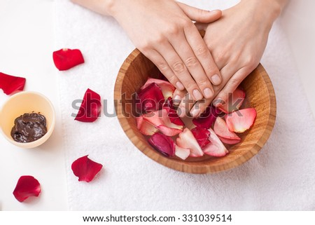 Close up of arms of young woman treating her skin at spa. She is keeping her hands in bowl with water and petals. There is brown substance on table - stock photo
