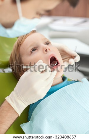 Close up of arms with gloves of experienced dental doctor. The man is examining teeth of kid. The boy is sitting in dental chair and looking up with fear. His mouth is wide open