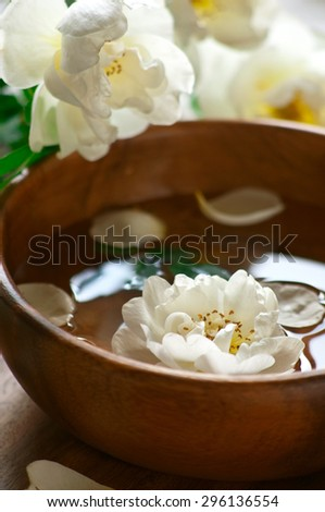 Close up of aroma spa set with white roses and wooden bowl, selective focus, vertical - stock photo