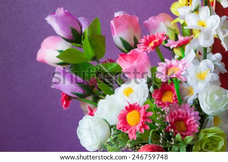 Close up of artificial flowers with wall - stock photo