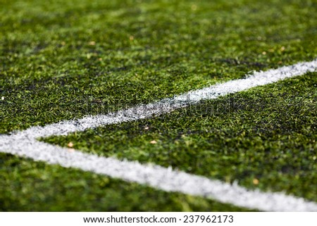Close-up of artificial green soccer turf on a sunny day.