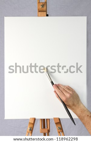 Close-up of artist starting to paint on a blank canvas on an easel, ready for adding your own image or text or design - stock photo