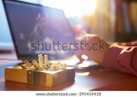 Close up of ashtray full of cigarette, with man in background working on laptop computer and smoking indoors on early morning. Concept of addiction and abuse of nicotine.  - stock photo
