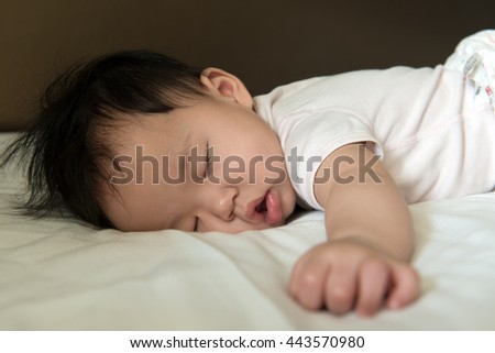 Close up of Asian baby sleeping soundly on bed - stock photo