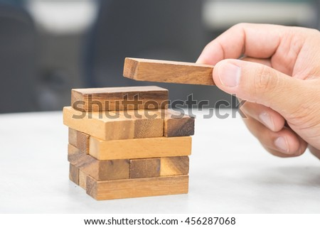 Close-up of asian business man's hand playing wood blocks stack game - stock photo