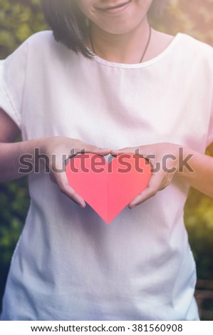 Close up of Asian girl white shirt smiling and holding red heart paper with two hands on natural plant background. soft focus. Sunlight.