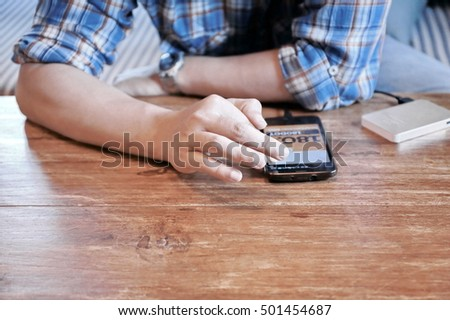 Close up of Asian man finger using mobile phone on sofa,young adult using mobile smart phone, Internet of things lifestyle with wireless communication and internet with smart phone.