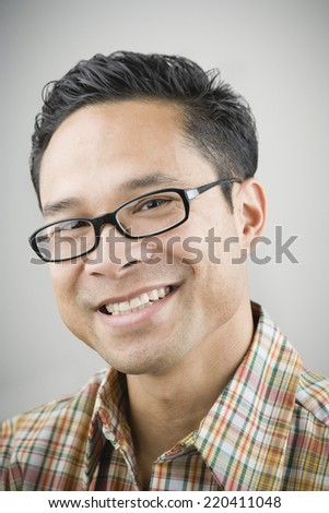 Close up of Asian man wearing eyeglasses and smiling - stock photo