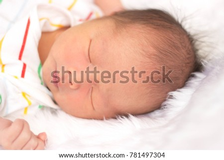 Close up of asian Newborn sleeping baby  on a white  wool .