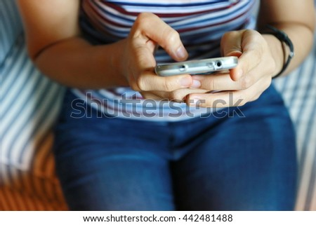 Close up of Asian woman hand using mobile phone on sofa,young adult using mobile smart phone, Internet of things lifestyle with wireless communication and internet with smart phone. - stock photo