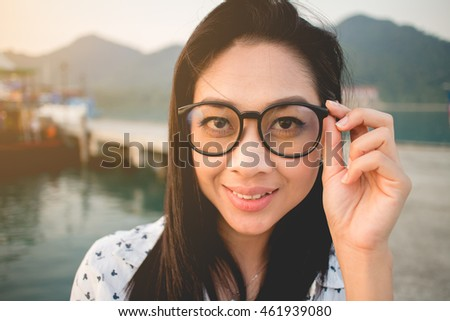 Close up of Asian woman with sunglasses on Thailand dock.