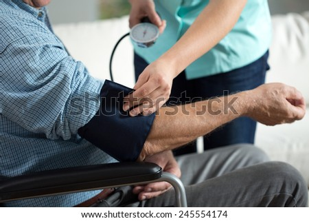 Close-up of assessment elderly patient's blood pressure  - stock photo
