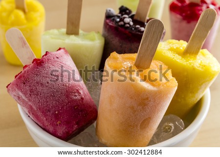 Close up of assorted flavors of homemade fresh pureed frozen fruit popsicles in white bowl with ice - stock photo