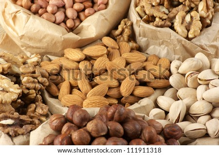 Close-up of assorted nuts in paper bags. - stock photo