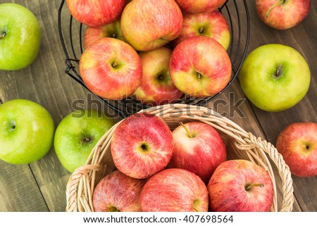 Close up of assorted ripe apples in a baskets and wooden background. - stock photo
