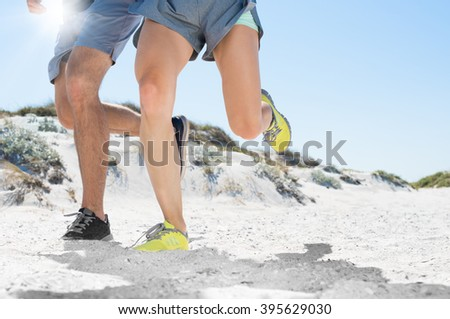Close up of athletic runners legs running on beach. Sporty fit couple jogging on sand during outdoor workout. Human legs running on sandy beach, copy space. - stock photo