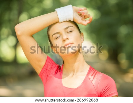 Close-up of athletic young woman after training outdoors in the morning. - stock photo