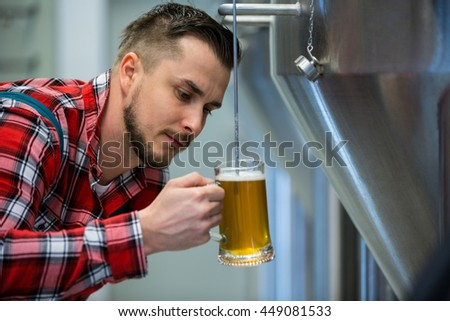 Close-up of attentive brewer testing beer at brewery