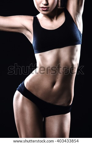 Close up of attractive and slim woman. Studio shot of young sporty woman on black background - stock photo