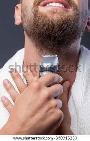 Close up of attractive man shaving his beard. He is holding electric razor and smiling. There is white towel on his neck - stock photo