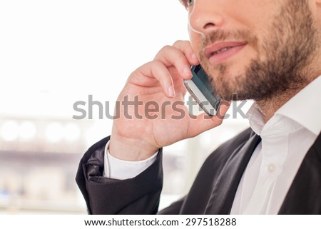 Close up of attractive man talking on the telephone with his business partner. He is serious an self-confident - stock photo