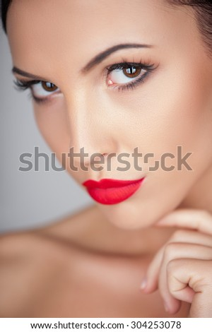 Close up of attractive woman is looking at the camera flirtingly. She is touching her chin with desire - stock photo