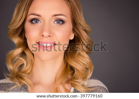 Close up  of attractive young smiling woman on gray background - stock photo