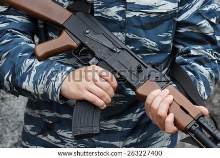 Close up of automatic weapon  in hands of military man in urban warfare. Selective focus