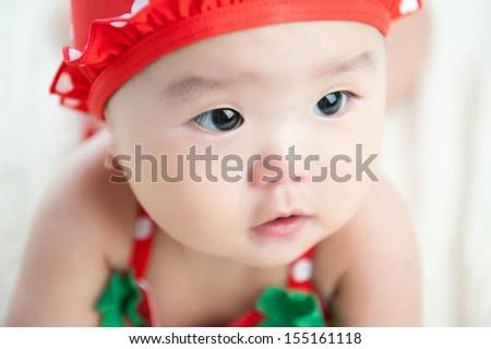 Close up of Baby in bikini, hat and sunglasses isolated on white blanket - stock photo