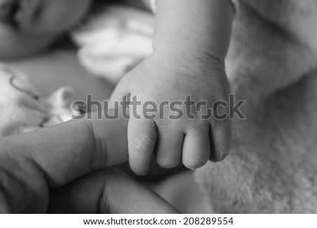Close-up of baby's hand holding mother's finger with tenderness, black and white - stock photo