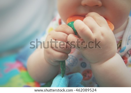 Close up of baby's hands holding on a toy and biting it