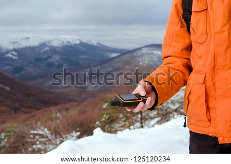 Close up of backpacker holding in his hand GPS navigator, Global Positioning System device. Mountain winter landscape as a background. - stock photo