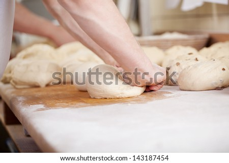 Close-up of baker kneading the dough of bread rools