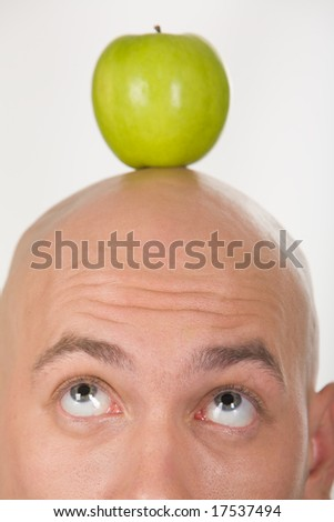 Close-up of bald head with green apple on its top - stock photo