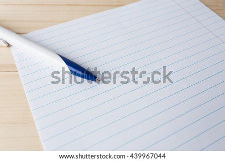 close-up of ball point pen over lined paper - stock photo