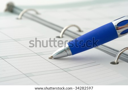 Close-up of ballpoint pen on open notebook - stock photo