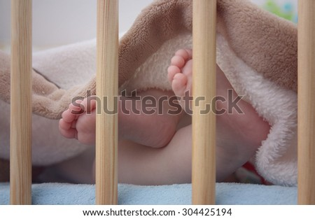 Close up of bare baby feet in bed
