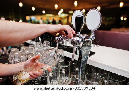 Close up of barman hand at beer tap - stock photo