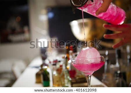 Close-up of bartender hand pouring pink cocktail drink in bar - stock photo