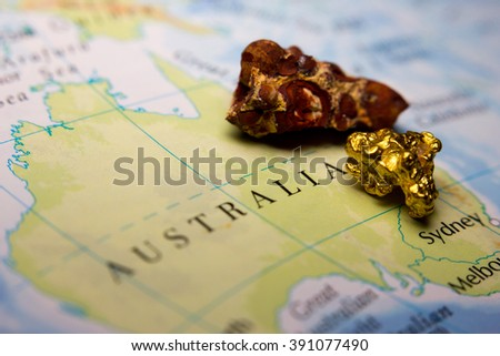 Close-up of Bauxite mineral and gold nugget on top of a map of Australia - stock photo