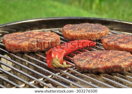 Close-up Of BBQ Hamburger Patties And Chili Pepper On The Hot Charcoal Grill. Vibrant Backyard Lawn In The Background. Cookout Food For Summer Weekend Picnic Or Party.