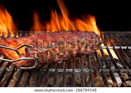 Close-up Of BBQ Roast and Smoked Pork Baby Back Spareribs On The Hot Charcoal Grill With Flames Isolated On Black Background - stock photo