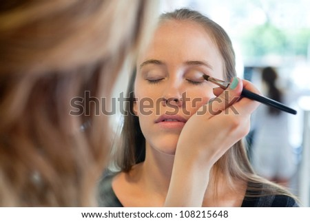 close up of beautician applying eye shadow to woman at parlor - stock photo