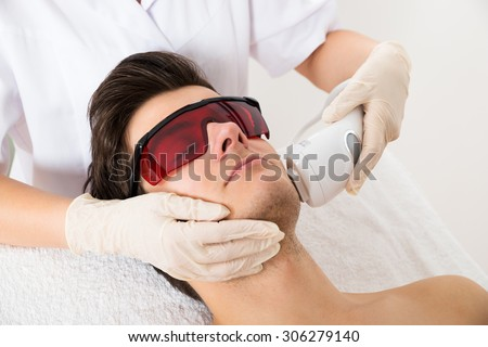 Close-up Of Beautician Giving Laser Epilation Treatment To Young Man Face - stock photo