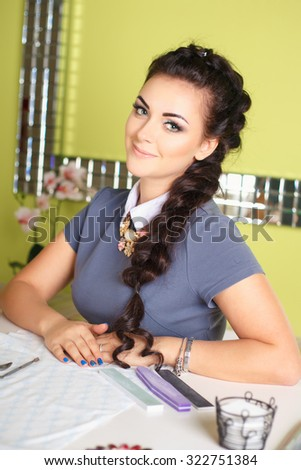 Close-up of beautician young brunette woman. manucurist women sitting in spa salon and smiling