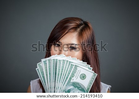Close up of beautiful Asian girl  with dollar bills close her lower face on gray background - stock photo